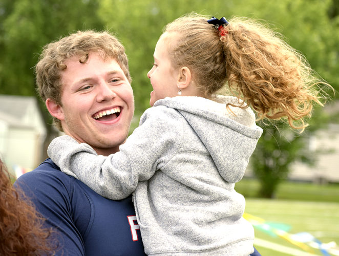 Tribune Chronicle / John Vargo Austintown Fitch's Brent Fairbanks gets a hug from his cousin Brooklyn Hall on Wednesday after winning the Division I regional boys discus title.