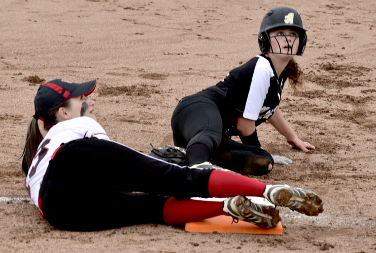 Tribune Chronicle / Eric Murray Mathews second baseman Emily Derkach, left, and Kylee Knott of St. Thomas Aquinas await the call of the umpire on a pickoff play at first base Friday at Kent State University. Knott was called out after Derkach took a throw from catcher Alivia Oulton. Mathews defeated Aquinas, 6-3, in the Division IV regional semifinal.