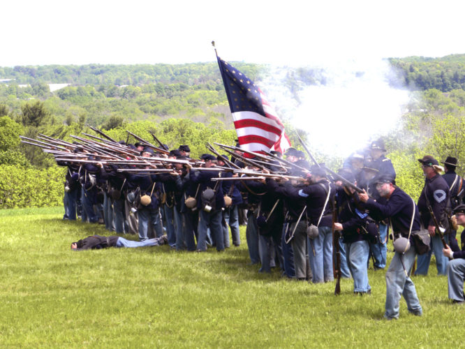 Union riflemen prepare to fire during a battle at the Civil War re-enactment, which is part of the encampment event. There also is crafts, food, music and open houses at several of the village buildings.