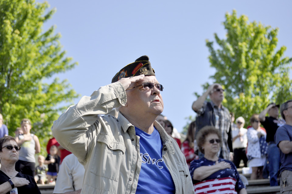 Jerry Kopiak, a veteran of the Marine Corps, salutes as the Star Spangled Banner is sung Monday.