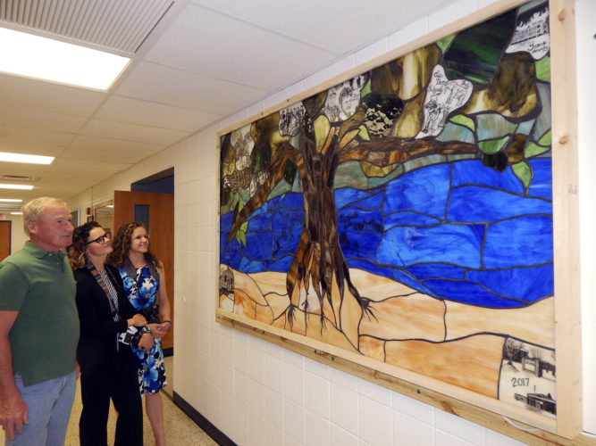 Tribune Chronicle / Bob Coupland Ted Rupe, a retired Maplewood teacher, and Maplewood alumni Jeni Butler and Holly Jones look at a stained-glass art in the high school hallway depicts the history of Maplewood Local Schools. The project was completed by art students in Jordan Moxley's classes at the high school.