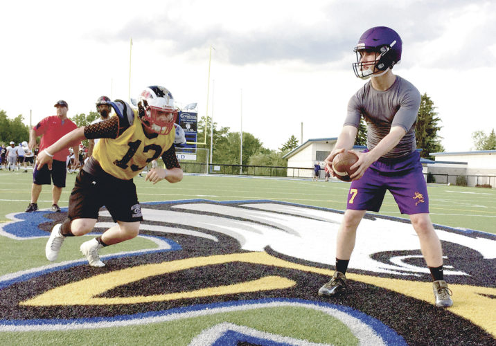 Tribune Chronicle / Joe Simon Champion's Brandon Allen, right, prepares to hand off to Niles' Tyler Srbinovich during a practice for the Jack Arvin All-Star Classic football game at Hubbard.