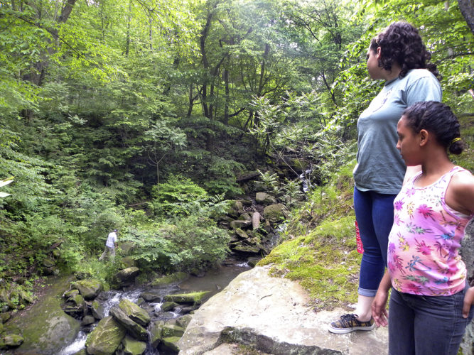 Kiara Lutz, 10, right, and Cierra Mosholder, 18, both of Austintown, watch Frankie Sainz, 24, of Beaver Falls, Pa., scale the rocks in the Homewood Stone Quarry that lead to the cascading water known as Buttermilk Falls in Homewood, Pa.    Tribune Chronicle photos /  Virginia Shank