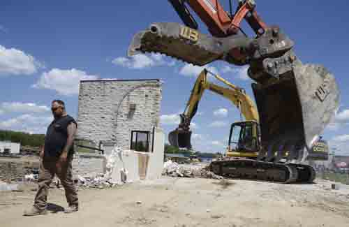 Tribune Chronicle /                       R. Michael Semple   Rick Uhl with Woodford Excavating of Braceville walks back to his excavator as demolition continues on the former Four Seasons Car Wash along Elm Road in Bazetta where construction of a new ALDI store is scheduled to begin June 23.