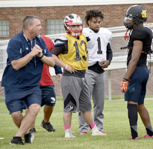Tribune Chronicle / Joe Simon Coach Dan Williams, left, demonstrates a play to Tyler Srbinovich (13), Lynn Bowden (1) and Tyriq Ellis, right, during a practice for the Jack Arvin All-Star Classic football game. Williams is coaching in the game for the second time — and he's having fun doing it.