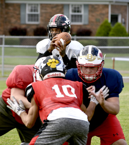 Tribune Chronicle / Joe Simon Warren G. Harding quarterback Lynn Bowden takes the snap as Niles' Joey Kendall, right, provides protection during a recent Jack Arvin Classic practice in McDonald.
