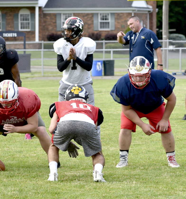 Tribune Chronicle / Joe Simon Former Warren G. Harding quarterback Lynn Bowden, center, awaits the snap from LaBrae's Alec Jerina, left, as Niles' Joey Kendall, right, guards Bowden. McDonald coach Dan Williams, who is mentoring the Trumbull team in tonight's Jack Arvin Classic, looks on during a recent practice in McDonald.