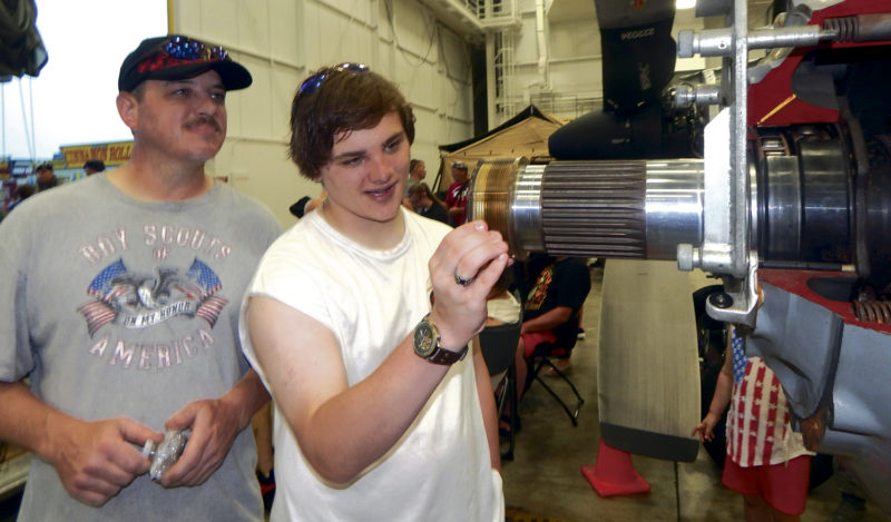 Walter Danko of Champion, left, spent Father's Day with his family, including a son, Devin Danko, 17, looking at planes and other displays Sunday at the Thunder Over the Valley Air Show in Vienna. Severe storms shortened the event.