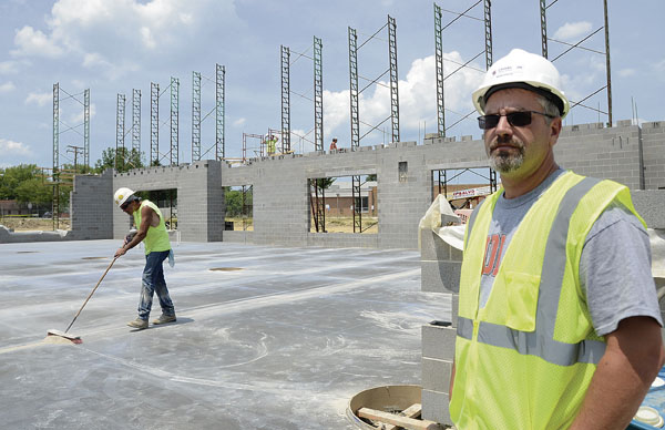 Champion schools facility manager Mark Harper stand next to the first concrete pour as construction continues on the new PK-8 school.. by R. Michael Semple