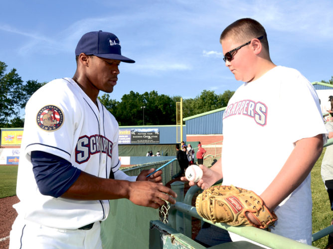 Tribune Chronicle / R. Michael Semple  Mahoning Valley Scrappers outfielder No. 7, Will Benson, left, autographs a baseball for Carsen Sharpe, 12, of Niles before the start of Wednesday's home opener at Eastwood Field. The Scrappers lost 3-2 to the Auburn Doubledays.