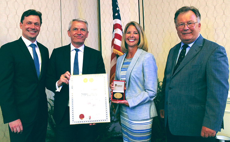 Kim Lody, president, GN Hearing North America, holds the Diploma of the Danish Export Association and HRH Prince Henrik's Medal of Honor. Lody, a Newton Falls High School graduate, was recognized by Denmark officials earlier this month for her efforts in promoting and marketing Danish products and services.
