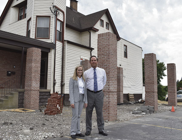 Tribune Chronicle / Renee Fox   Funeral directors Jillian Kinnick and her father, Tom Kinnick, partner at the Kinnick Funeral Home in Girard, stand in front of the under-construction car port that is being partially funded by a downtown revitalization grant coming from Trumbull County.
