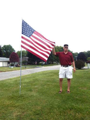 Tribune Chronicle / Bob Coupland The Howland Rotary has started a fundraiser to get U.S. flags in yards throughout the community. Ken Abell, Howland Rotary community service chair, places a flag in a yard. Flags are placed by the Rotary twice a year from May to July and September to November.