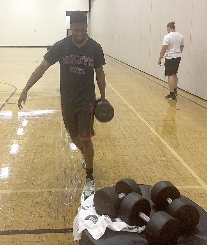 Tribune Chronicle / John Vargo YSU men's basketball player Cameron Morse walks with a weight during a recent training session.