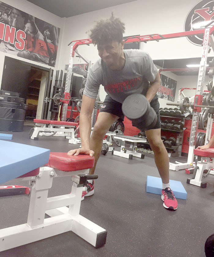 Tribune Chronicle / John Vargo Youngstown State men's basketball player Michael Akuchie lifts during a recent weight room session.