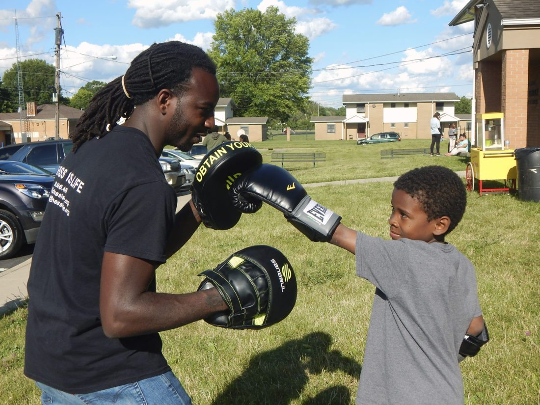 Tribune Chronicle photos / Bob Coupland Myles Jay, left, instructs Azariyon Foster, 8, on Zumba boxing at the Highland Terrace weekly community gathering in Warren. Children take part in chess, Zumba boxing, arts and crafts and other activities each Tuesday evening.
