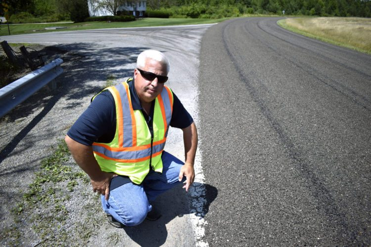 Tribune Chronicle / Renee Fox Tom Klejka, Trumbull County highway superintendent, explains the county's new process for road chip-and-seal projects Tuesday on Scoville North Road in Vienna. The county now is using sifted road grindings from other roads milled during the paving process, which Klejka said should save money.