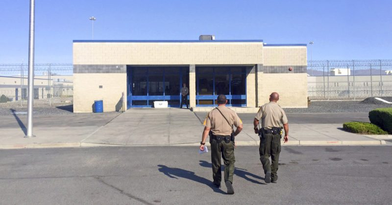 Officers walk toward the entrance to Nevada's Lovelock Correctional Center in Lovelock, Nev., where former NFL football star O.J. Simpson is being held Thursday, July 20, 2017. Simpson is making the case on live TV for his release from prison where he has been serving a 33-year sentence for an armed robbery involving sports memorabilia. (AP Photo/Terry Chea)