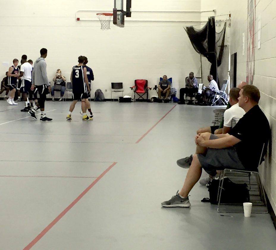 Youngstown State men's basketball coach Jerrod Calhoun, right, watches an AAU tournament last week in the Columbus area. College basketball coaches keep busy during July visiting numerous tournaments to find the players they need.