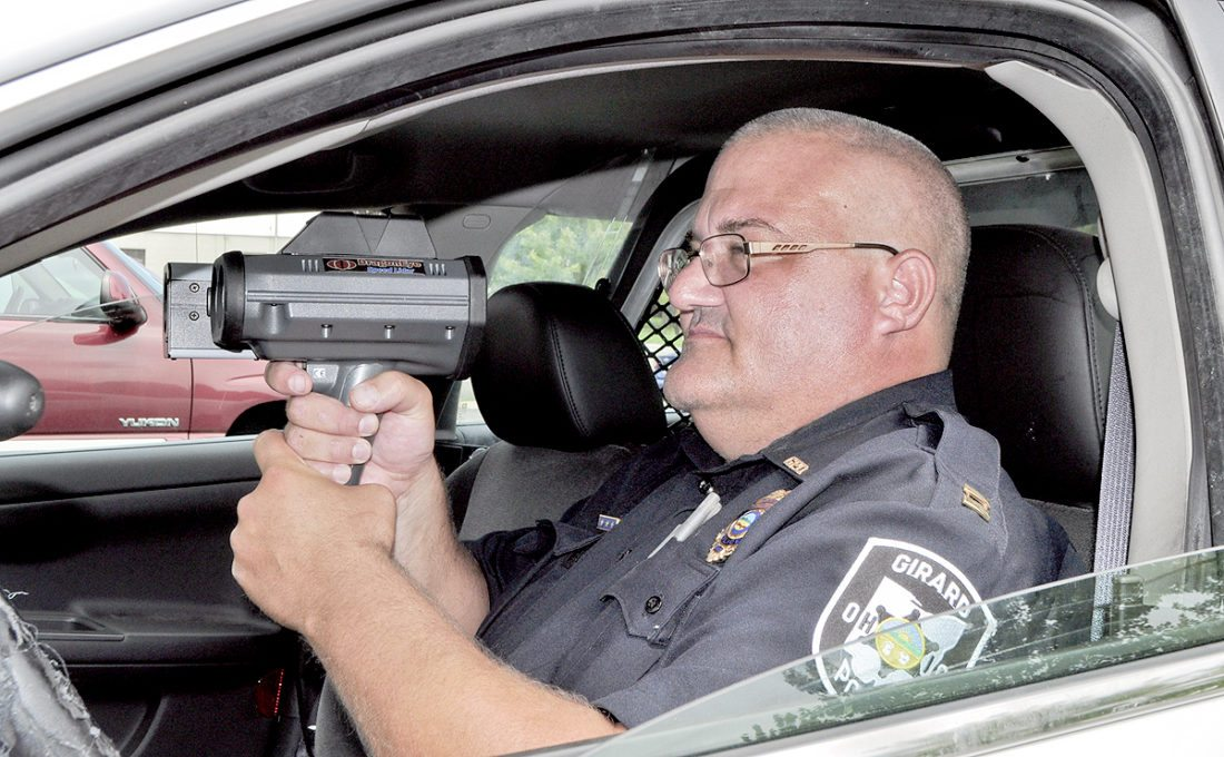 Tribune Chronicle file photo Girard police Capt. Rich Bznak aims a handheld speed camera at traffic as vehicles travel through the city. The Ohio Supreme Court ruled Wednesday home-rule communities like Girard can go back to having unmanned traffic cameras, but Girard is staying with the handheld machines.