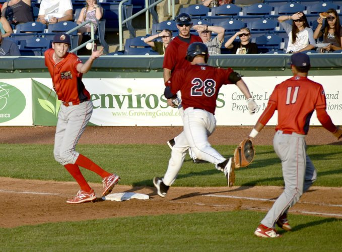 Tribune Chronicle / Joe Simon Williamsport starting pitcher Kyle Young, left, reaches to catch the ball and tries to tag first base before Mahoning Valley's Simeon Lucas (28). Young caught the ball, a flip from the Crosscutters first baseman Nerluis Martinez (11), but missed the base and Lucas was safe on the play.