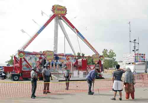 AP Passers-by look at the Fire Ball ride as Ohio State Highway Patrol troopers stand guard at the Ohio State Fair Thursday in Columbus.  The fair opened Thursday but its amusement rides remained closed one day after Tyler Jarrell, 18, was killed and seven other people were injured when the thrill ride broke apart and flung people into the air.