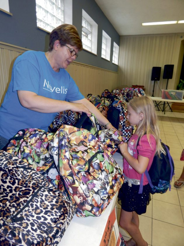 Tribune Chronicle / Bob Coupland Julie Harman, human resource leader for Novelis in Warren, left, assists Breanna Harris, 6, of Warren, select a backpack filled with school supplies Thursday at the Warren Family Mission. Novelis purchased the backpacks and school supplies for more than 450 local children.