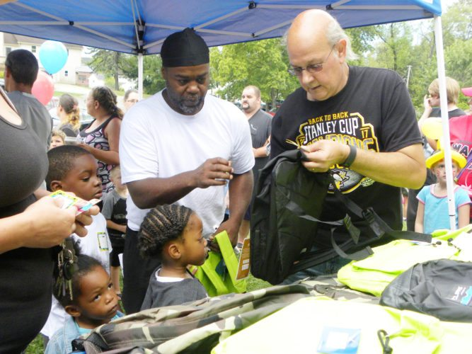 Tribune Chonicle / Emily Earnhart Robert Thompkins, 32,  and his children, Dion, 6, Skylar, 4 and Nova, 3 of Youngstown get book bags for the new school year from 6-year volunteer, Tom Breda, 58, at the Lena Mason Christian Memorial Foundation Annual Free Family Fun Day and Book bag giveaway at Tod Park in Girard.
