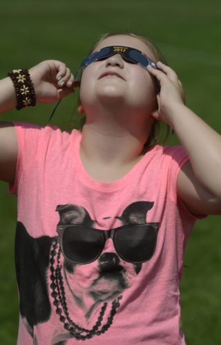 Tribune Chronicle  / R. Michael Semple  ABOVE: Bristol third-grader Maddison Pineda, 8, wearing her special outfit for the solar eclipse, looks skyward with her special glasses as the moon passed partially in front of the sun Monday afternoon.