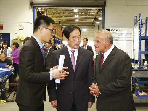 Tribune Chronicle / Virginia Shank  Xiangen Hu, chairman of CW Group, center, discusses CW Bearing's recent acquisition of Drake Manufacturing in Champion with Trumbull County Commissioner Frank Fuda, right. Hu's assistant, Leon Jiang, left, helps the Chinese businessman translate his comments into English.