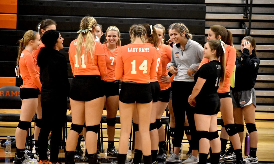 Tribune Chronicle / Eric Murray Mineral Ridge volleyball coach Joey DeLisio, left, shares a laugh with her team during a break in the Rams' three-set victory Wednesday night over Liberty. The Rams are off to a 3-1 start as they try to reach their goal of having a winning season.
