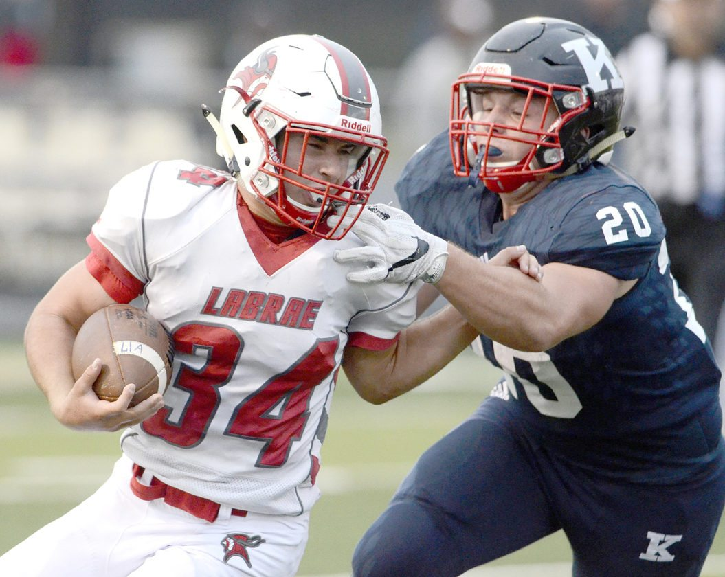 090117...R LABRAE 7...Warren...09-01-17...LaBrae #34 Colton Stoneman rushes for yardage as JFK's #20 Isaac Hadley goes for the tackle during 1st half action...by R. Michael Semple