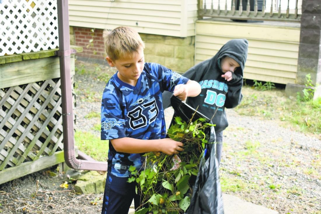 Tribune Chronicle / Renee Fox Donovan Brown, 9, and A.J. Jenyk, 9, helped their parents clean up a lawn Saturday on Ann Avenue in Niles.
