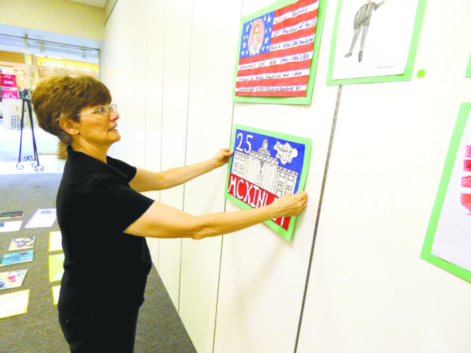Tribune Chronicle / Andy Gray Mariann O'Halloran, fiscal officer for the McKinley Memorial Library, hangs entries for the McKinley Art Contest Show, which opens Friday at the Art Outreach Gallery at Eastwood Mall in Niles.