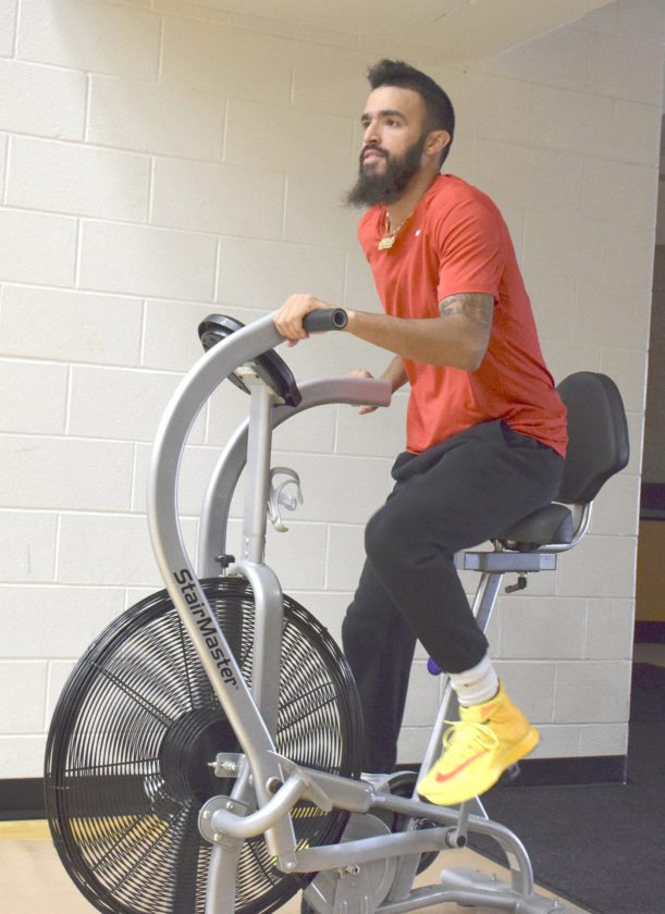 YSU senior point guard Francisco Santiago works out on a stationary bicycle recently at the Beeghly Center. Santiago is recovering from a hyper-extended knee which held him out of the summer workouts. He is now participating in fall workouts and is full-go with the brace he'll wear throughout the upcoming season.