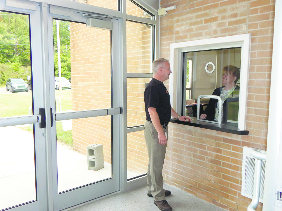 Tribune Chronicle / Bob Coupland Howland School Supertintendent Kevin Spicher stands inside a new vestibule at Howland Middle School. Each of the district's six school buildings has a new vestibule.