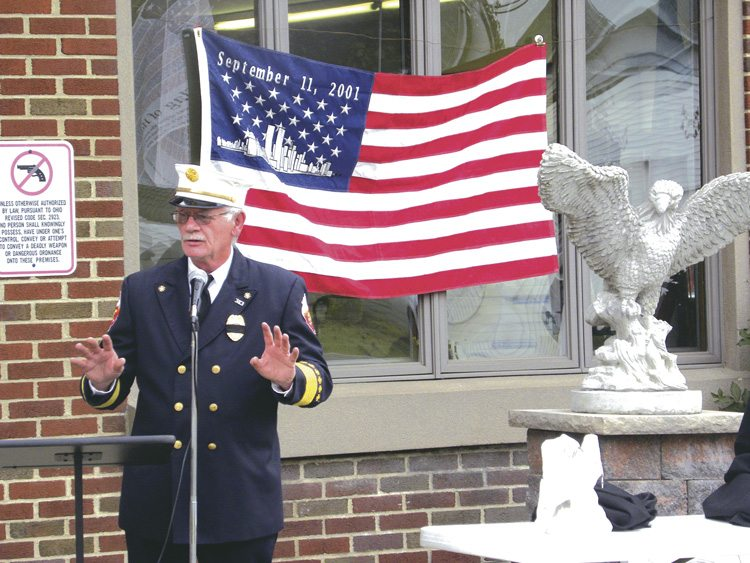 Tribune Chronicle / Lexy Cummins Vienna fire Chief Richard Brannon speaks Monday evening at the fire department's 9/11 memorial ceremony. The small eagle to the right is an urn that holds dirt from the crash site of Flight 93 in Shanksville, Pa. It's now part of the department's memorial.