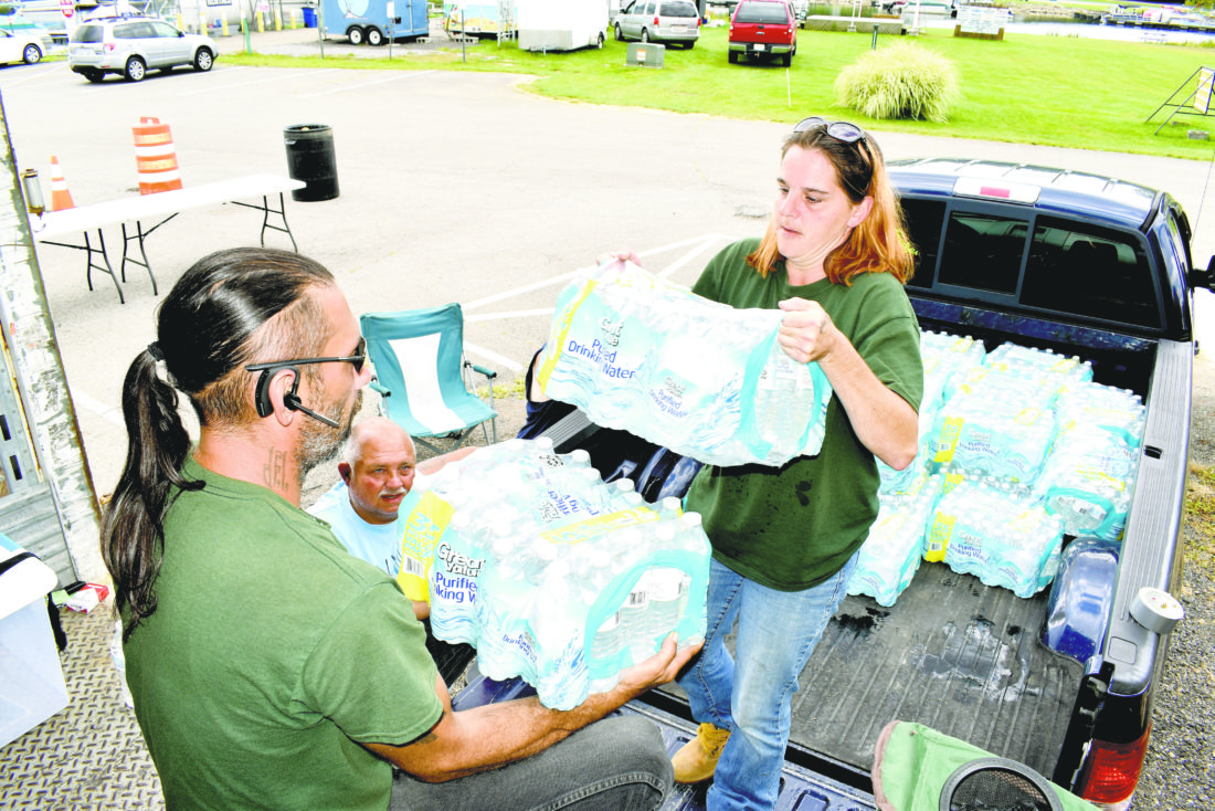 Tribune Chronicle / Renee Fox Kevin Lemon, left, and Kim Chitwood, both with Tree Trimmin' Express, load 50 cases of bottled water onto a 57-foot trailer Wednesday as part of a collection for Hurricane Irma victims in Florida. The company donated the water, the trailer and its employees' time. Supervising the work is Joe Sofchek with the Mosquito Lake State Park Marina, where the collection is being held through Sunday.