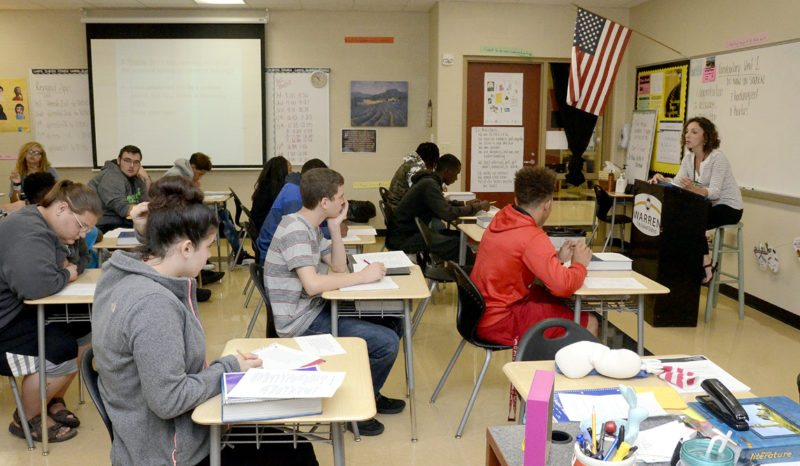 Tribune Chronicle / R. Michael Semple Warren G. Harding High School teacher Logan Hileman, far right, teaches 11th-grade English Thursday, which is the same day the Ohio Department of Education released the 2016-17 State Report Cards. Results show Warren City Schools K-3 literacy rates improved from an F last year to a C this year and the district also improved its four-year graduation rate.