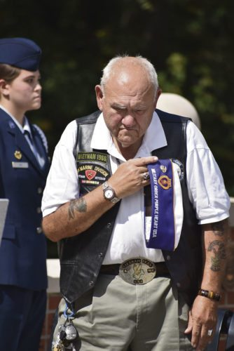 Ken Lewis bows his head during the Laying of te Roses ceremony Friday in Warren in honor of Vietnam and Operation Iraqi Freedom veterans who lost their lives. Joon Kim, with the Air Force ROTC program at Trumbull Career and Technical Center, in the background, led the ceremony.