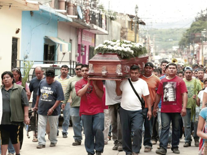 AP Locals carry the casket of a woman who died in Tuesday's earthquake, in Tlayacapan, Morelos state, Mexico, Wednesday. People by the millions rushed from homes and offices across central Mexico after a 7.1 earthquake, sometimes watching as buildings they had just fled fell behind them with an eruption of dust and debris. The earthquake killed at least 230 people.