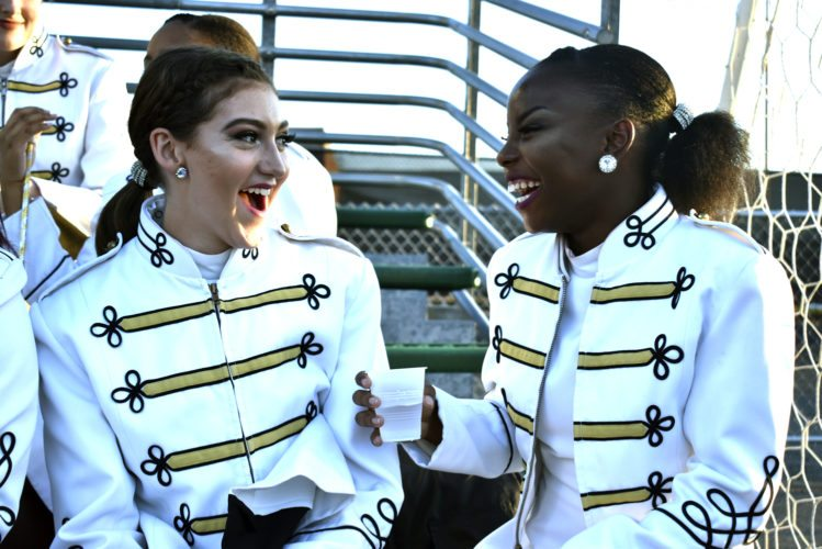 Tribune Chronicle  / Renee Fox Warren G. Harding High School majorettes Jillian DiCesare (left), senior, and Nadia Moore, junior, wait to perform Saturday in the school's 58th annual band night. The evening, rescheduled after a storm disrupted the event in August, fell during the city's homecoming weekend and took place on a day with a record-breaking temperature of 89 degrees.