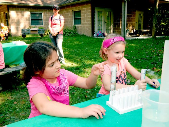 Tribune Chronicle / Bob Coupland Annabelle Campos, 7, of Warren, left, and Ariana Johns, 6, of Warren, look at dry ice in test tubes as they make ''potions'' at the Girl Scout camporee held at Camp Sugarbush in Vernon. The theme included activities relating to Harry Potter.