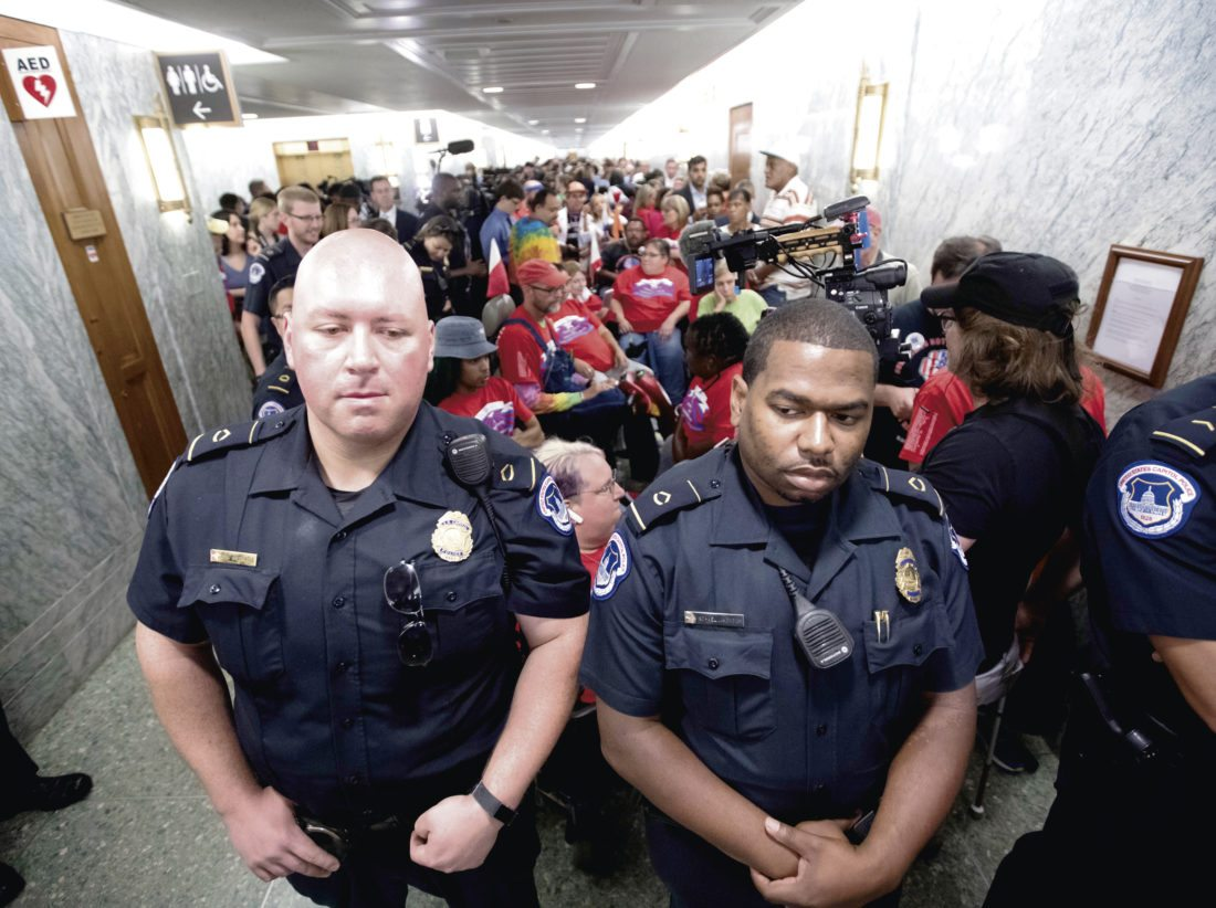 U.S. Capitol Police maintain order as hundreds of people, many with disabilities, arrive for a Senate Finance Committee hearing on the last-ditch GOP push to overhaul the nation's health care system, on Capitol Hill in Washington, Monday, Sept. 25, 2017. (AP Photo/J. Scott Applewhite)