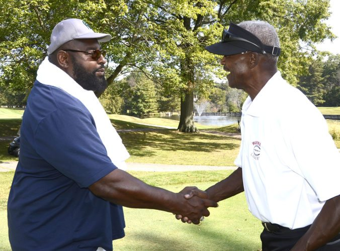 Tribune Chronicle / R. Michael Semple Warren Legends Travis Davies, left, and Paul Warfield shake hands while attending the Warren Legends Golf Outing at Trumbull Country Club Monday...by R. Michael Semple