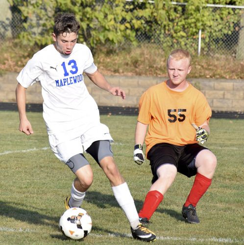 Tribune Chronicle / John Vargo Maplewood's Thomas Rink (13) tries to get past Bloomfield goal keeper Harry Houser Wednesday at Maplewood.