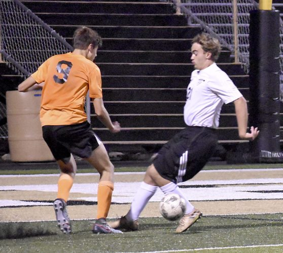 Tribune Chronicle / Marc Weems Howland's Manny Perez (9) tries to get past Warren G. Harding's Michael Clauss Thursday night at Mollenkopf Stadium. The Tigers beat the Raiders, 3-0.