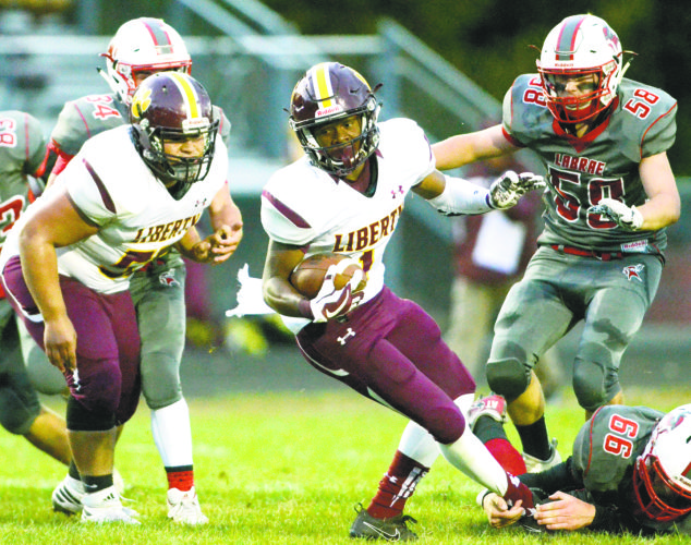 Tribune Chronicle / R.Michael Semple Liberty's Dra Rushton, middle, twists and turns as he tries to break the tackle attempt of LaBrae's Riley McCleary during the first half. Liberty's Simi Moananu, left, and LaBrae's Konner Johnston (58)follow the play. Liberty beat the Vikings, 34-20, in an All-American Conference, Blue Tier matchup.