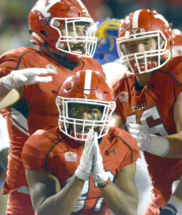 Tribune Chronicle / R. Michael Semple YSU's Tevin McCaster, center, celebrates a score with teammates Saturday in his team's 19-7 win in Youngstown.