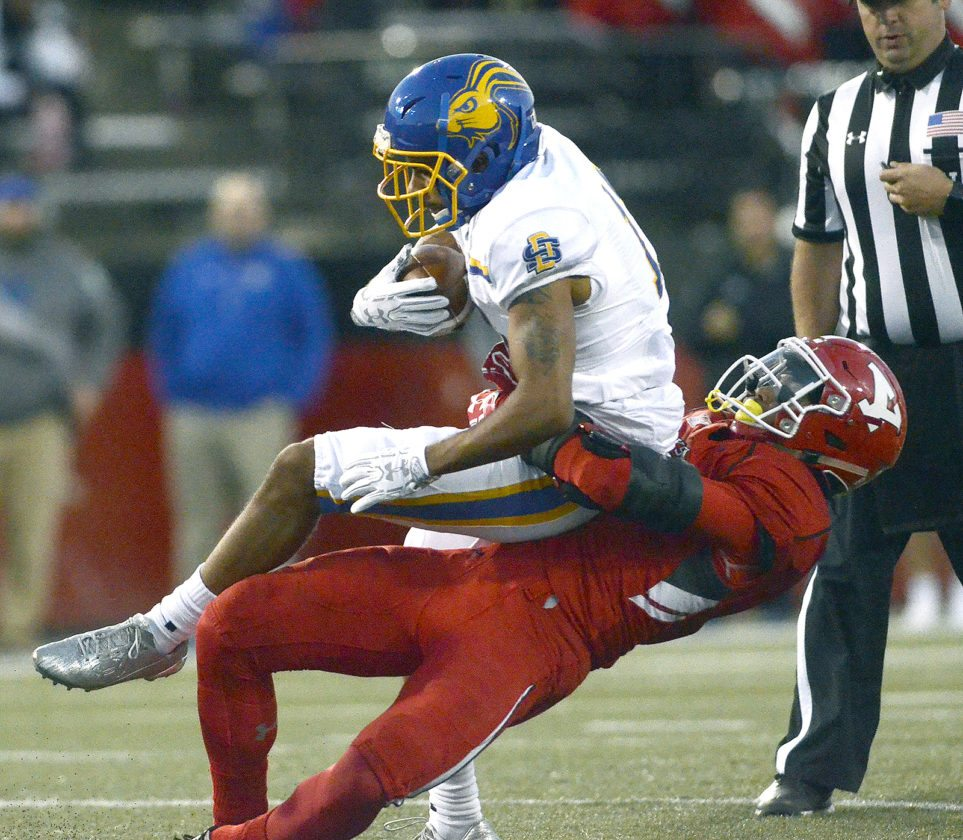 Tribune Chronicle / R. Michael Semple YSU's Kyle Hegedus stops South Dakota State's Marquise Lewis after a first-half reception.